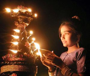INDIAN GIRL LIGHTS A DEEPAWALI LAMP IN AHMEDABAD